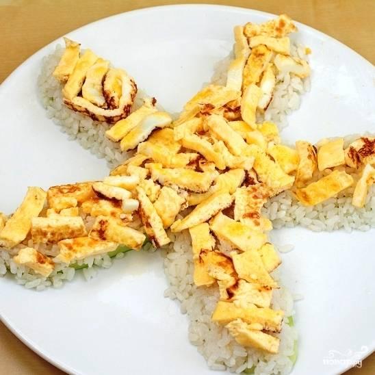 На рис намазываем сливочный сыр, на него выкладываем нарезанный полосками омлет. Опять же, не спешите, делайте все аккуратно - иначе торт получится некрасивым.