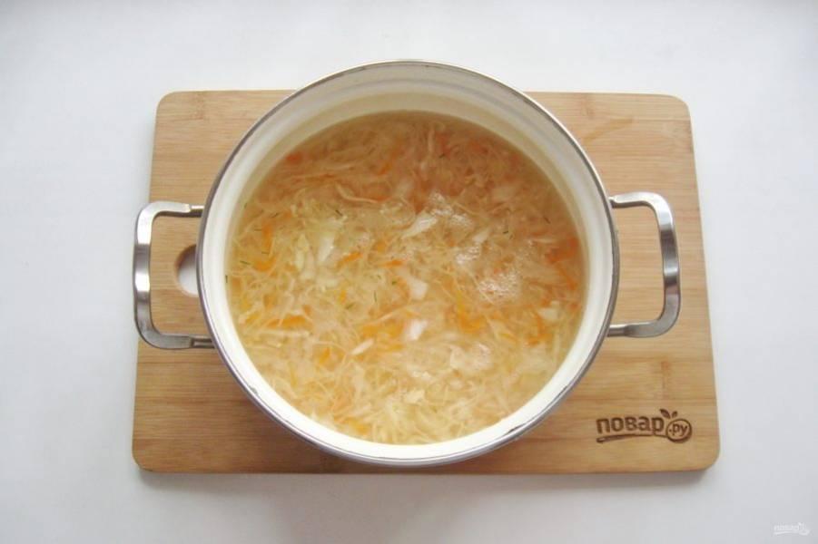 В кастрюлю налейте бульон и выложите квашеную капусту. Поставьте на плиту и варите 25-30 минут до мягкости капусты.