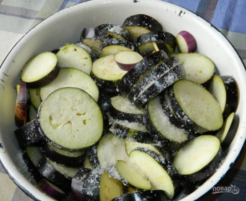 Нарежьте баклажаны кружочками, посолите и оставьте на некоторое время. Это необходимо для того, чтобы ушла горечь.