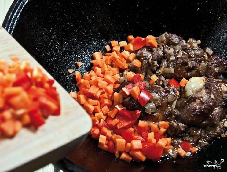 Для данного блюда нам понадобится чугунная посуда. Лучше всего подойдет казан, чугунок или что-то подобное. Можно использовать глубокую сковородку с толстыми стенками и дном. Обжариваем мясо на растительном масле почти до готовности. Закладываем овощи: сначала — лук, а потом уже морковь и болгарский перец. Помидоры кладем последними.