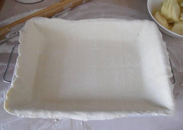 1. Чтобы приготовить картофельный пирог с мясом в домашних условиях в кратчайшие сроки можно использовать готовое слоеное тесто. Для начала его необходимо немного разморозить и раскатать на поверхности, присыпанной мукой. Пласт теста должен быть немного больше формы, в которой будет выпекаться пирог. На дно формы можно положить пергамент для выпечки или немного смазать ее маслом. Выложить раскатанный пласт теста.