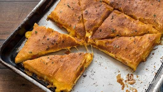 В разогретую до 180 градусов духовку поставьте пиццу минут на 12-14. Разрежьте ее на порции и подавайте теплой.