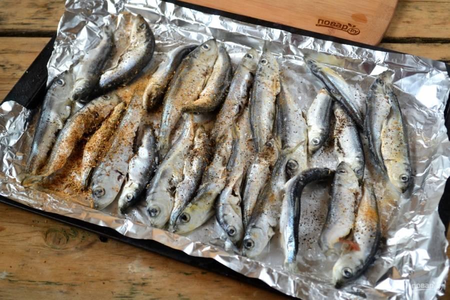 Присыпьте кильку специями, перцем и солью. Сбрызните льняным маслом. Я советую использовать именно это масло, оно придает рыбе особый аромат, к тому же оно невероятно полезное, поэтому его стоит хоть понемногу добавлять во все блюда.