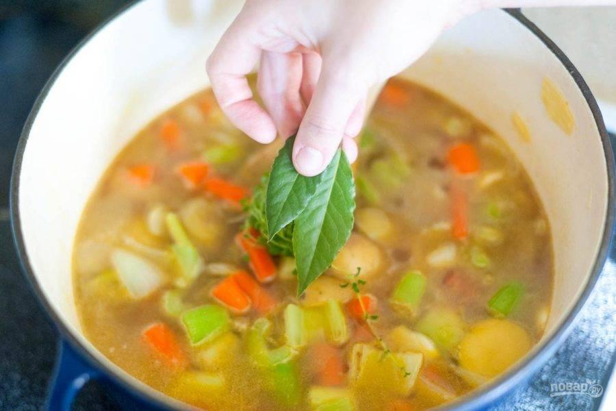 Греем в сковороде масло и готовим овощи 10 минут, добавив соль, перец тимьян. Затем вливаем бульон и кладем лавровый лист.