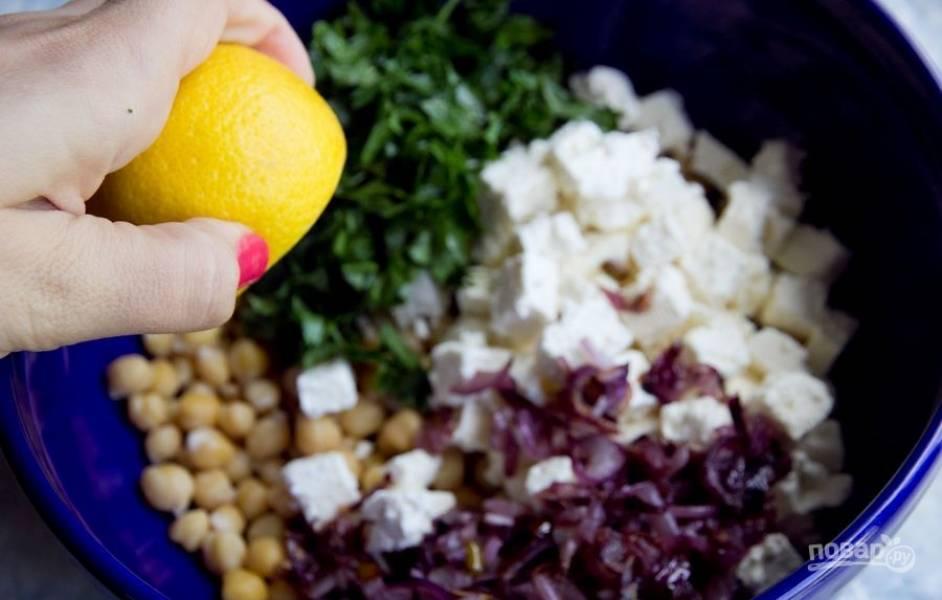 В салатнице соедините мелко нарезанную зелень, зажарку, фету и нут. Влейте сок лимона.