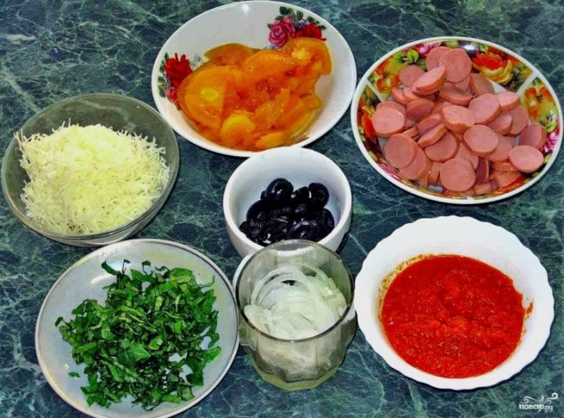 Берем сосиски, помидоры, маслины и лук. Нарезаем все колечками, так, чтобы было красиво. Вместо кетчупа можно взять домашнюю аджику. Базилик и орегано можно запросто заменить любой зеленью. Подойдет все, что вы кладете в салат. Зелень измельчаем.