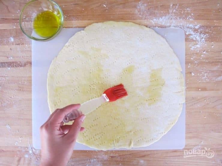 Тесто раскатайте на присыпанной мукой поверхности, наколите вилкой и смажьте маслом.