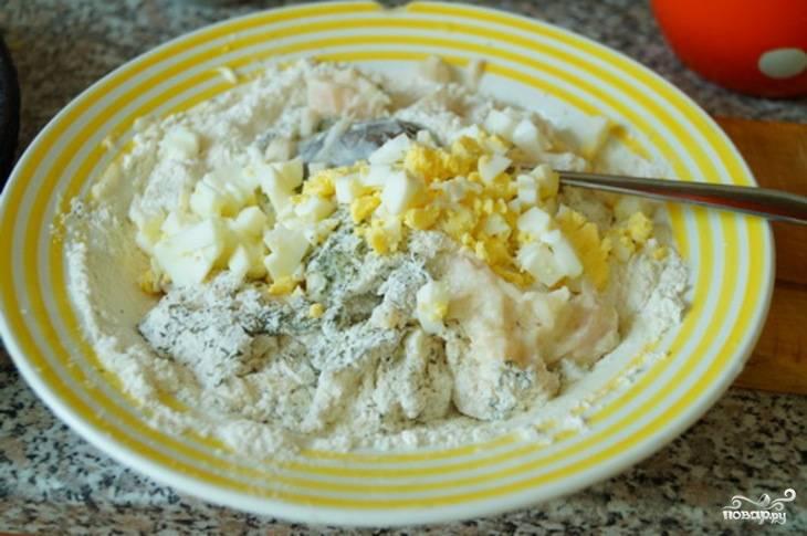 Выкладываем рыбу в тарелку и добавляем к ней майонез, муку, сырое куриное яйцо, измельченные вареные яйца и петрушку. Теперь солим и посыпаем молотым перцем, тщательно перемешиваем все ингредиенты.