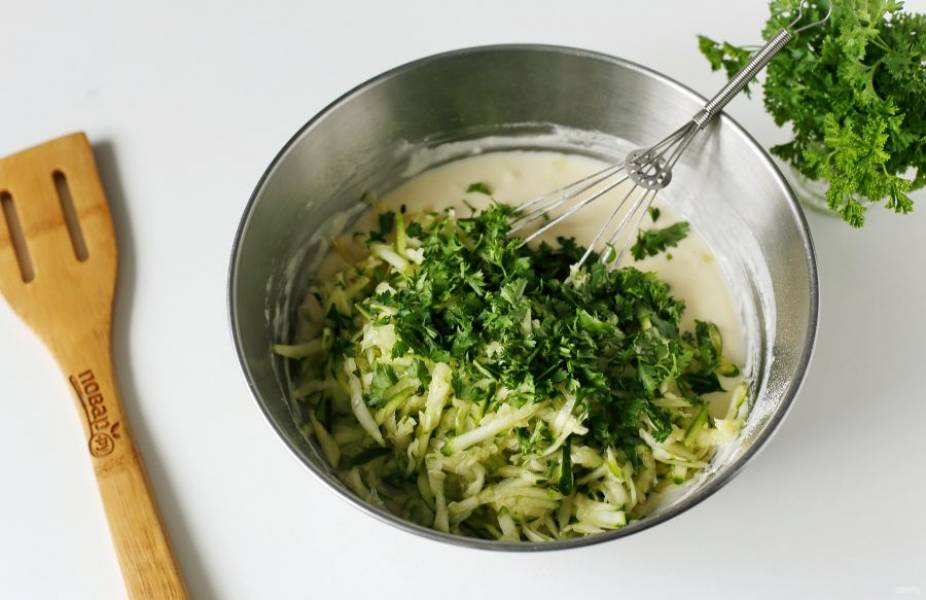 Перемешайте все до однородного состояния, добавьте отжатый кабачок и измельченную зелень.