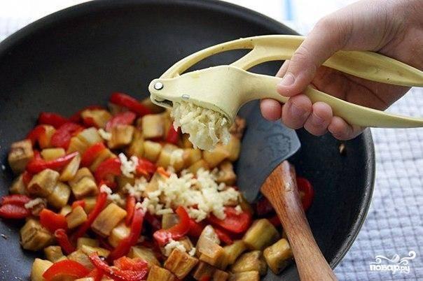Далее в сковородку кладем промытые от соленной воды баклажаны, нарезанный соломкой болгарский перец и выдавливаем чеснок. Овощи обжариваем, постоянно перемешивая.