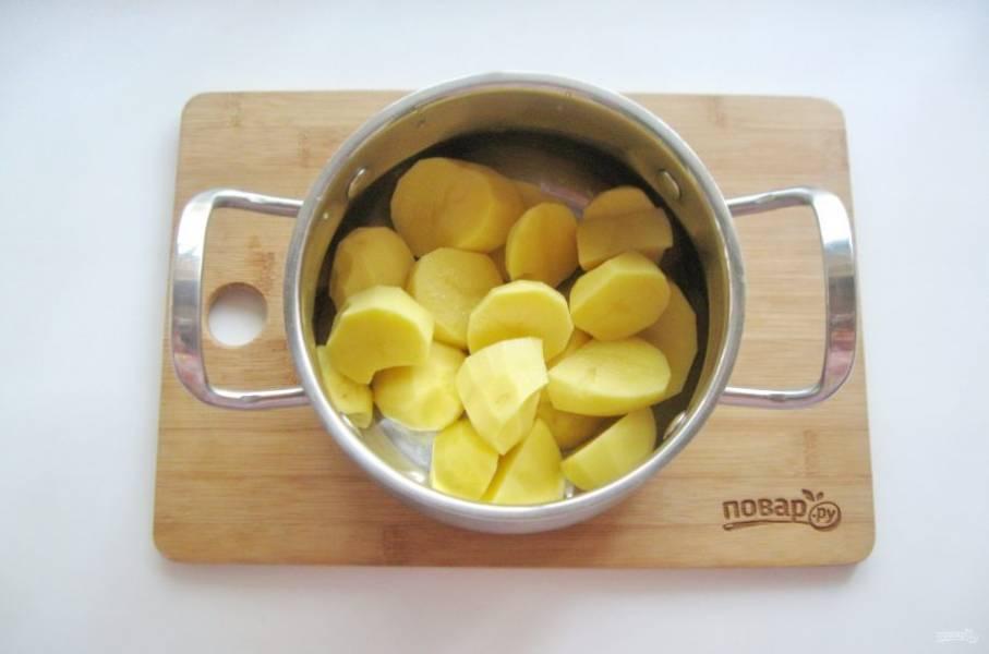 Картофель хорошо помойте, после очистите и опять тщательно помойте.  Крупный картофель нарежьте и выложите в кастрюлю.