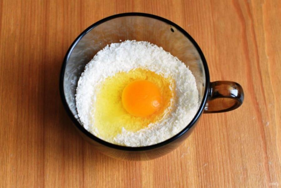 Для начинки смешайте кокосовую стружку с размягченным сливочным маслом и сахаром, добавьте яйцо и тщательно перемешайте массу вилкой до однородности.
