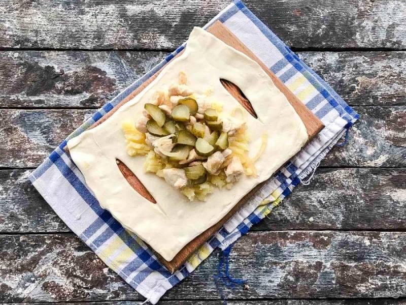 В центр заготовки поместите начинку, сначала выложите картофельное пюре, сверху курицу и огурцы. Сформируйте лодочки. Потяните полоски к центру, перекрестите над начинкой и расположите их внахлест на противоположные края.