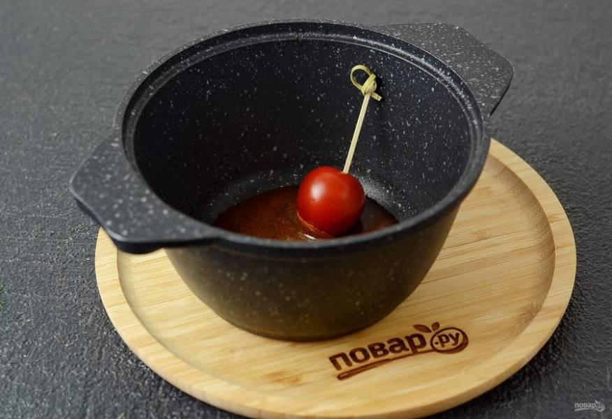 Снимите кастрюлю с плиты. Пару секунд остудите. Обмакните каждый томат в карамель на 5 секунд.