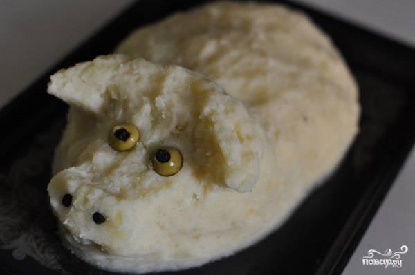 3. А теперь самый интересный и творческий процесс - выложите сверху пюре так, чтобы получилась свинка. По сути, нужно обмазать форму из капусты картофельным пюре. Сформируйте ушки и пятачок. Глазки можно сделать из оливок и горошин перца. Плотно прижмите пюре руками и уберите форму в холодильник часа на 4 (можно на ночь).