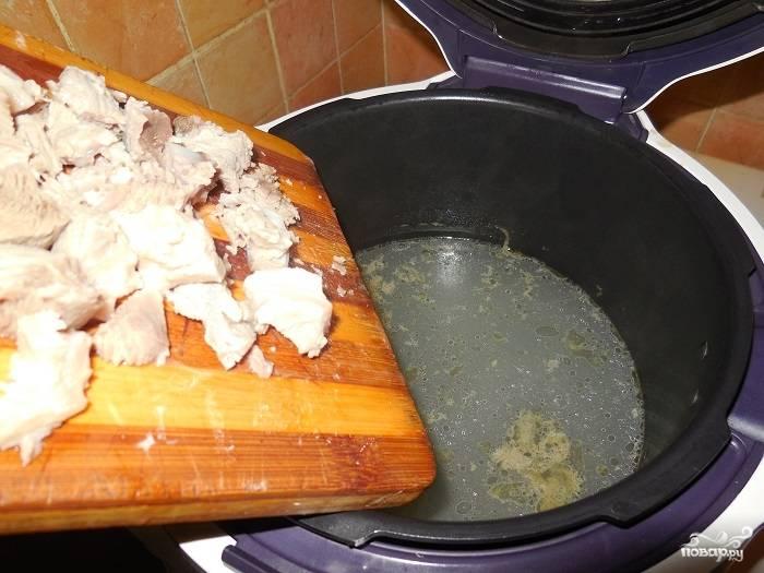 Свинину готовую достаньте из бульона, порежьте ее на кусочки. Снова верните в бульон.