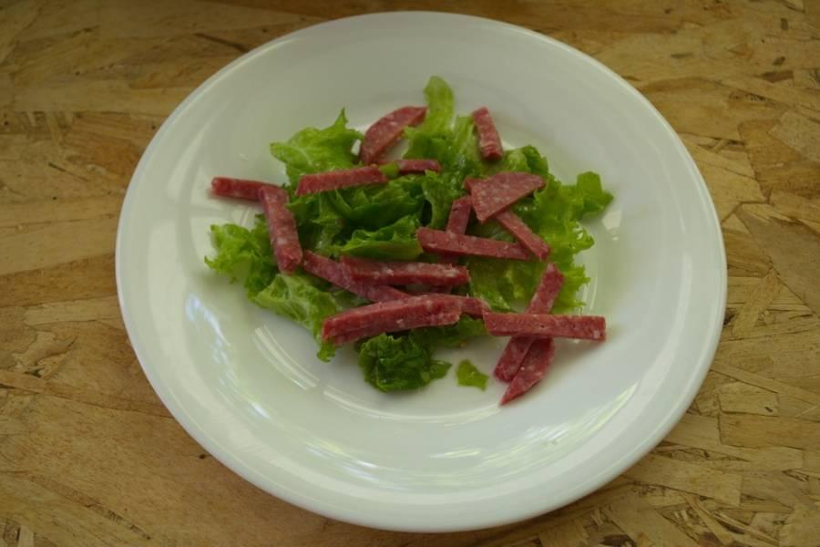 Колбасу  нарезаем брусочками и выкладываем на листья.