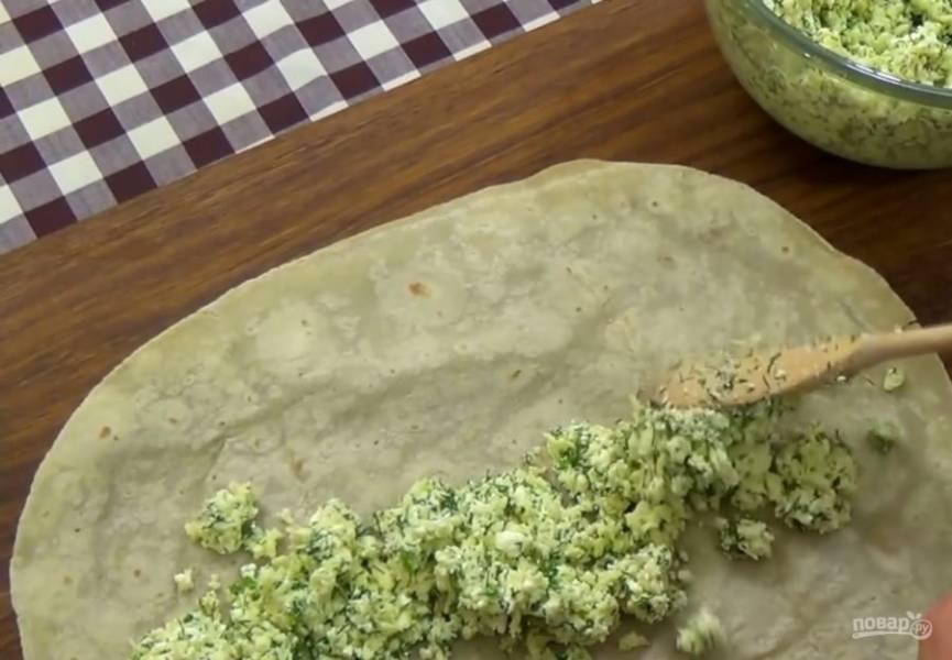 2. Выложите начинку тонким слоем на лист лаваша и скрутите его в неплотный рулет. Форму для выпечки застелите пергаментной бумагой и смажьте сливочным маслом. Выложите рулеты спиралью.