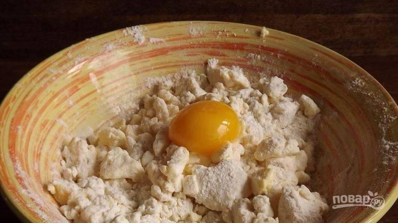 Руками перетрите творог с маслом в однородную массу. Затем возьмите сырое куриное яйцо, отделите желток от белка и добавьте желток к творогу с маслом.