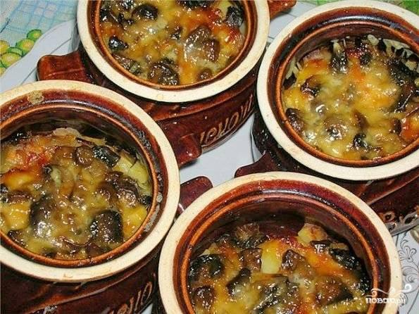 По истечению этого времени горшочки достать и посыпать их содержимое тертым сыром. опять отправить в духовку - на этот раз при 200С - на 15 минут, пока не образуется аппетитная сырная корочка. Подавать блюдо горячим.