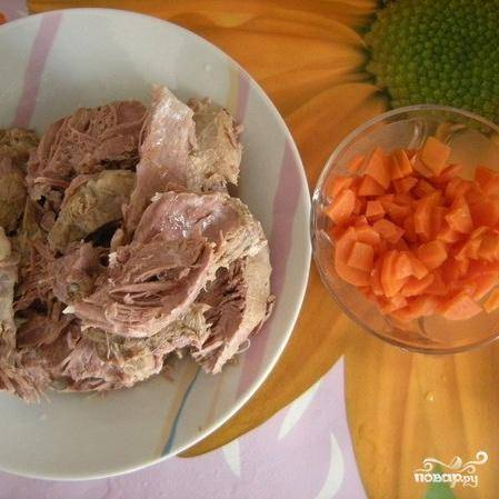 5.Сваренное мясо вынуть из бульона и нарезать на кусочки. Луковицу выбросить. Морковь нарезать ломтиками.