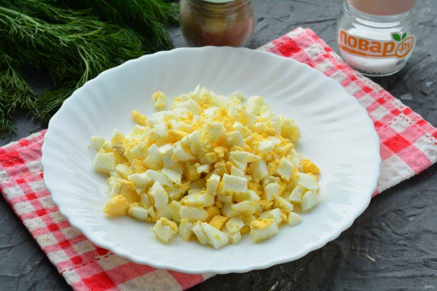 Сварите яйца вкрутую, варите 8 минут после закипания воды. Остудите яйца, почистите и нарежьте кубиками.
