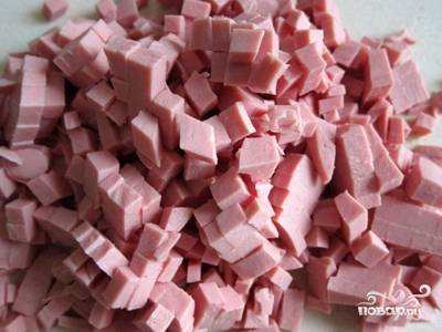 4. Помойте редис. Обсушите. Затем натрите его на крупной терке. Достаньте из холодильника колбасу. Снимите с нее оболочку. Затем нарежьте на аккуратные кубики.