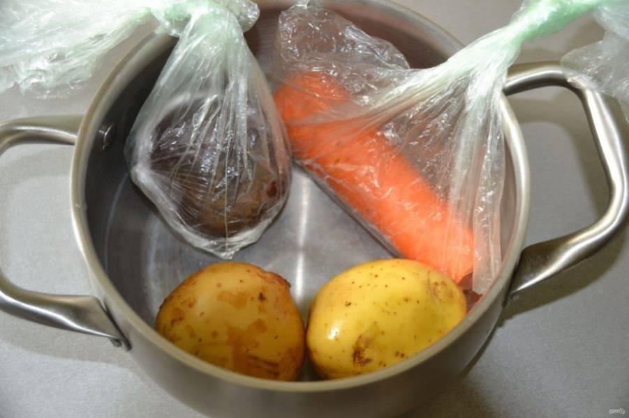 Отварите заранее куриную грудку, яйца, морковь, свеклу и картофель. Можно вот так, в одной кастрюле, свеклу и морковь отваривайте в пакетах.