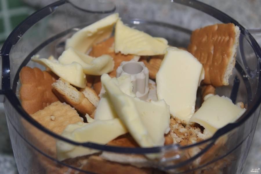 В блендере печенье вместе со сливочным маслом измельчите в крошку.