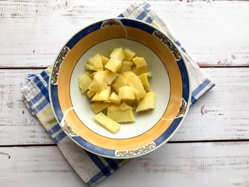 Остывший вареный картофель очистите и нарежьте кубиками.