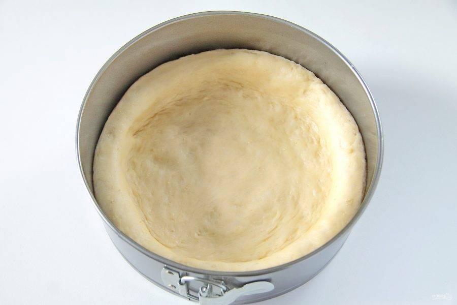 7. Переложите тесто в смазанную маслом форму и руками придайте ему форму лепешки с бортиками, высотой около 2 см. Накройте и оставьте примерно на 20 минут.