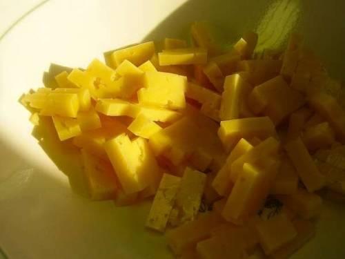 Сыр для блюда нужно выбирать как можно более твердого сорта с нейтральным вкусом. Нарезаем его небольшими кубиками или прямоугольниками, как на фото. Для того, чтобы продукт не приставал к ножу во время нарезки, лезвие нужно периодически смачивать в воде, а сам сыр перед измельчением немного подержать в холодильнике, 20 минут вполне хватит.