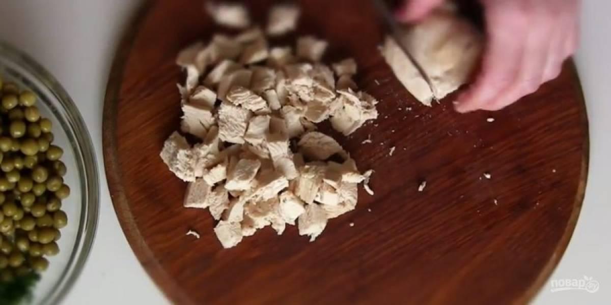 2. Куриное филе отварите, остудите и нарежьте небольшими кубиками. Добавьте филе к овощам, посолите по вкусу и заправьте салат сметаной.