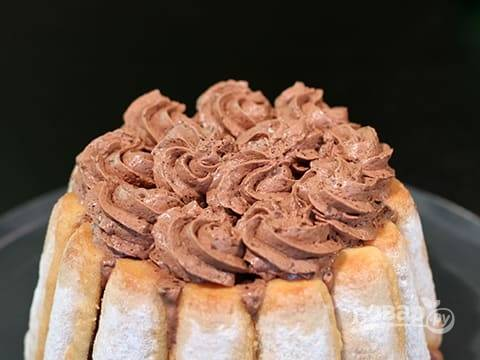 Украсьте торт оставшимся муссом и стружкой из белого шоколада.