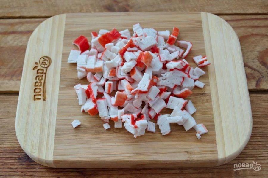 1.  Для приготовления салата Нептун возьмире крабовые палочки. Разморозьте их и нарежьте кубиком. Переместите нарезанные крабовые палочки в салатник.