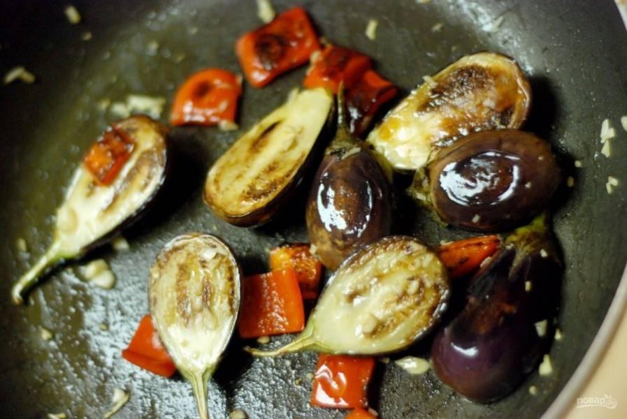 4.Спустя пару минут переверните баклажаны, добавьте нарезанный кубиками перец и крупно рубленный чеснок, обжаривайте несколько минут.