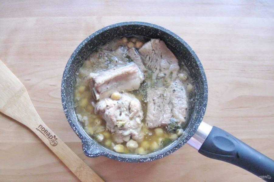 Накройте кастрюлю крышкой и тушите свиные ребрышки с нутом до готовности 1,5-2 часа. За 30 минут до окончания приготовления уберите петрушку, посолите и поперчите по вкусу. Оставьте блюдо под крышкой на полчаса, чтобы оно настоялось.