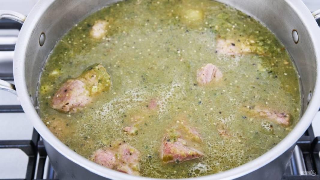 6.Влейте бульон в кастрюлю с мясом и добавьте измельченную в блендере смесь перцев с овощным физалисом. Если на дне кастрюли остались пригоревшие корочки с мяса, то соскребите их и все перемешайте. Добавьте в бульон мед, корицу, тмин, орегано и соль по вкусу. Доведите до кипения, уменьшите огонь и готовьте 2,5 часа.
