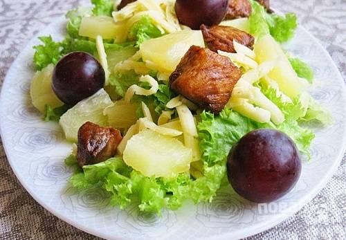 Смешиваем все подготовленные ингредиенты, выкладываем салат на блюдо и поливаем его заправкой. Можно украсить виноградом.