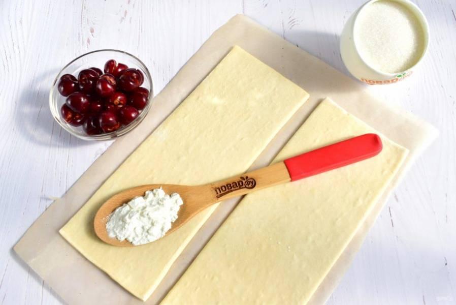 Замороженное слоеное тесто достаньте из морозильника, оставьте при комнатной температуре на 10 минут. Вишню без косточек откиньте на сито.