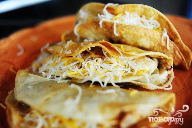 4. Готовые такос выложить на блюдо, удалить масло с помощью бумажных полотенец.   Посыпать тертым сыром.