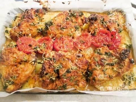 Выкладываем половинки помидоров, посыпаем крылышки и картошку сначала зеленью, а затем натертым сыром.