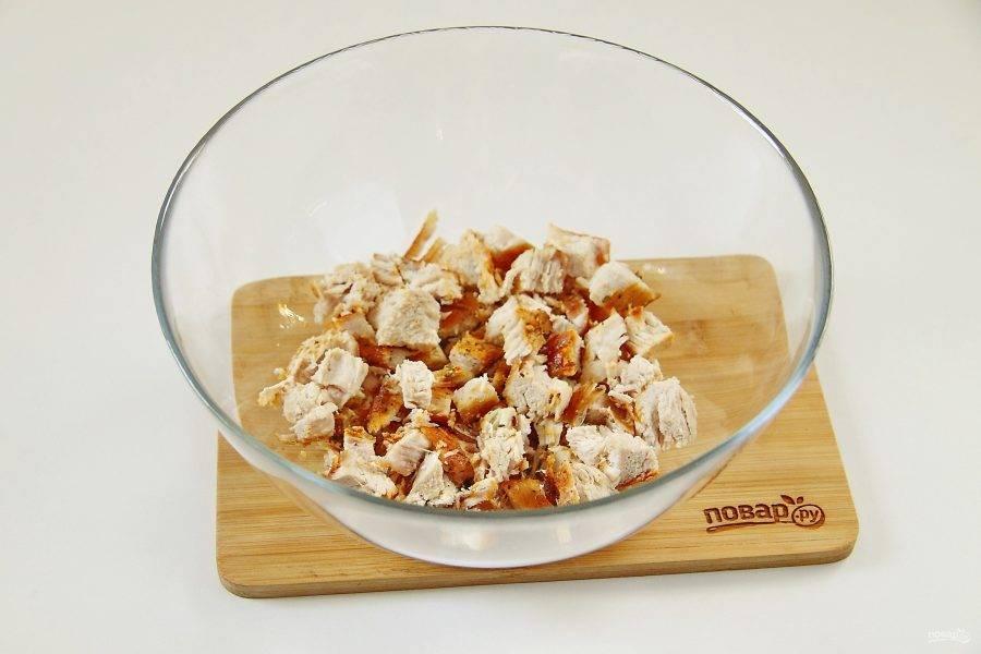 Нарежьте мясо небольшими кусочками и сложите в салатник или глубокую миску.