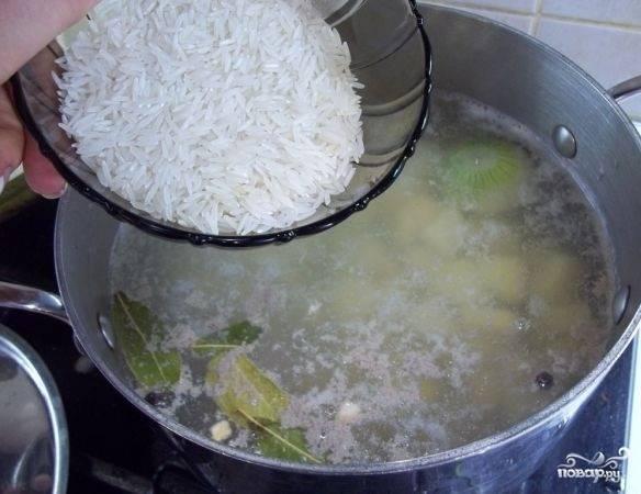 4. Когда мясо хорошо проварилось, аккуратно достаньте его и нарежьте небольшими кусочками. Отправьте обратно в кастрюлю вместе картофелем. Минут через 10 можно добавить промытый под проточной водой рис.