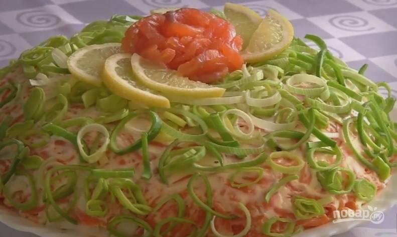 9. Украсьте салат колечками лука-порея, розой из красной рыбы и ломтиками лимона.