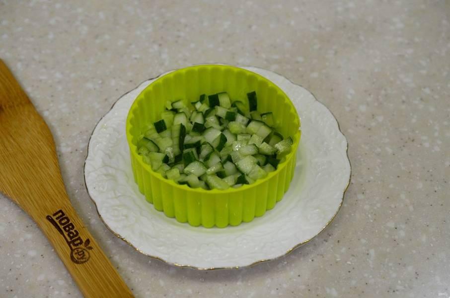 4. На тарелку поставьте сервировочное кольцо и выложите огурец первым слоем. Немного смажьте заправкой.