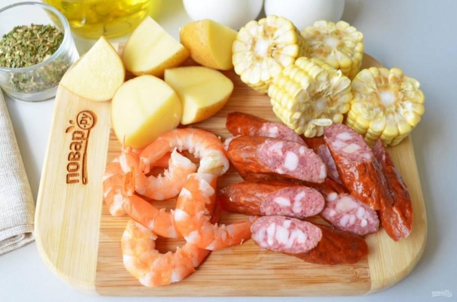 Порежьте картофель на 4 части, кочаны кукурузы — на части (любого размера), колбаски — наискосок. У креветок отрежьте головы, освободите их от панциря.