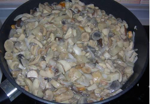 2. На растительном масле обжарим измельченный лук, пока он не станет прозрачным, а потом добавим грибы. Жарим все вместе до готовности. Солим и перчим по вкусу.