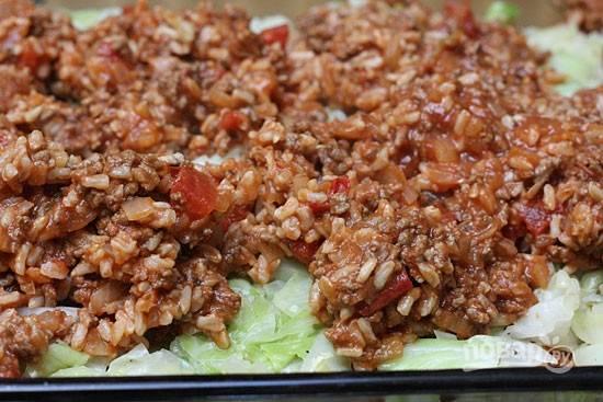 6. В жаропрочную форму выложите ровным слоем капусту, сверху — мясо с соусом. Присыпьте все тертым сыром, накройте фольгой и отправьте в разогретую до 180 градусов духовку.