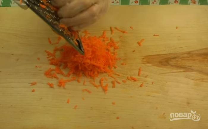 Очищенную морковь натрите на большой тёрке. Обжарьте около 5 минут морковь с луком в масле, постоянно помешивая.